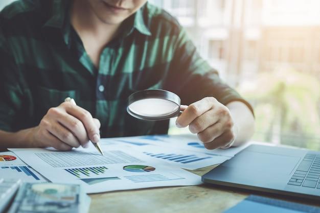 ビジネスマンのバランスを計算するためにラップトップコンピューターを使用して年次貸借対照表を確認するために拡大鏡を使用して。投資の概念の前に監査とチェックの整合性。 Premium写真