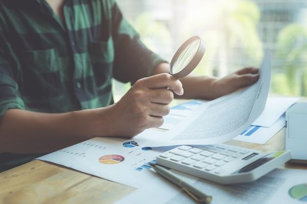 拡大鏡を使用してバランスシートを確認するビジネスマン Premium写真
