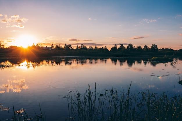 Красивый летний речной закат с красочными оттенками Premium Фотографии