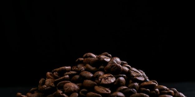 Аромат кофейных зерен лежат коркой на черном фоне. копировать пространство Premium Фотографии