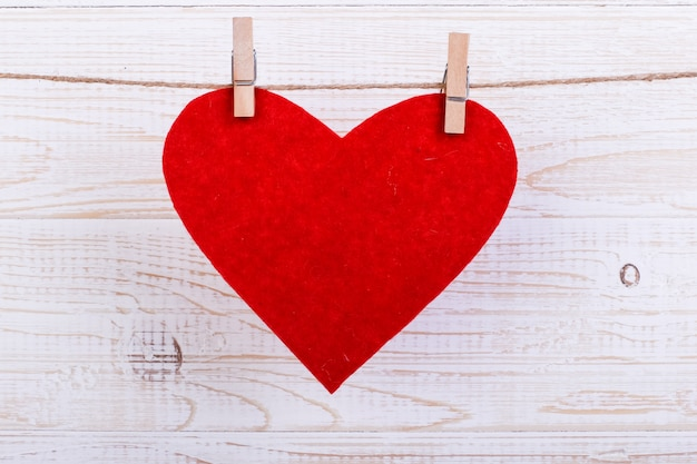 白い木製の背景に洗濯はさみでロープに赤いハート。テキストのための場所、スペースをコピーします。 Premium写真