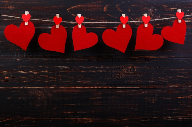 黒い木製の背景に洗濯はさみでロープに赤いハート。テキストのための場所、スペースをコピーします。 Premium写真