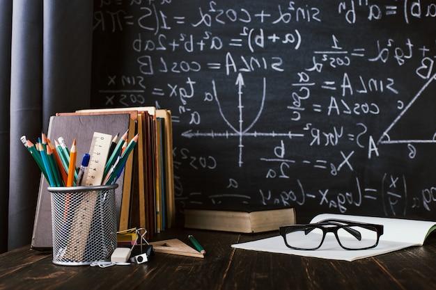 書かれた式とチョークボードの背景に関する書籍の教室でのスクールデスク Premium写真