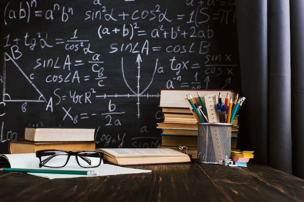Парта в классе, с книгами на фоне классной доски с письменными формулами Premium Фотографии