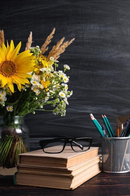 教師の日。黒いチョークボードと花瓶に新鮮な野の花 Premium写真