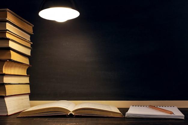 ランプの光の下で暗闇の中で黒板、本、ノート、ペンの背景に机。 Premium写真