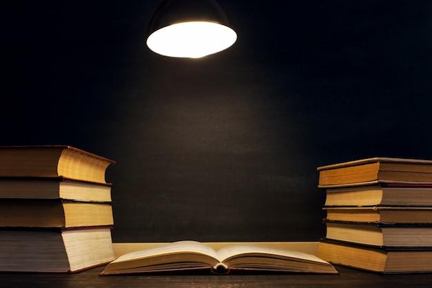 チョークボードの背景に机、ランプの光の下で暗闇の中で本。 Premium写真
