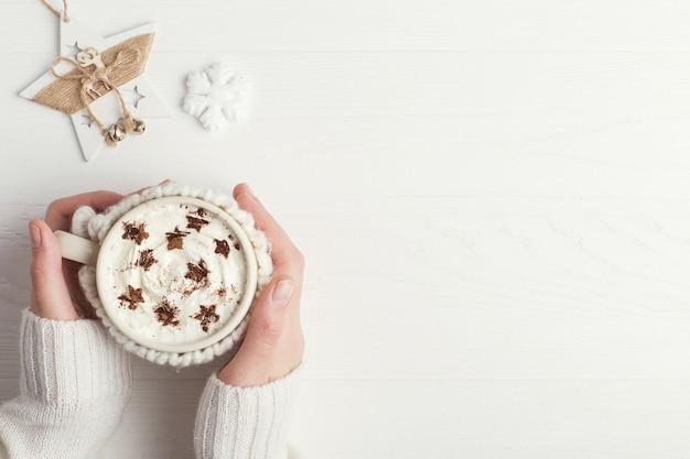 女の子は星の形のホイップクリームとパウダーで、熱い冬の飲み物のカップを保持しています。 Premium写真