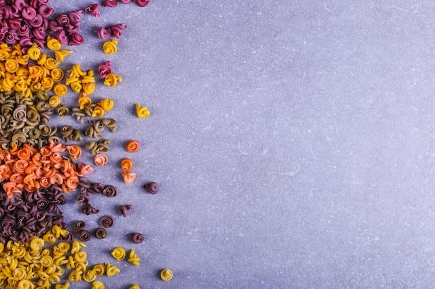 テーブルの背景のクローズアップに散在している天然野菜染料と珍しい形の色とりどりのパスタ。 Premium写真