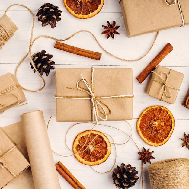 クラフトペーパー、ドライオレンジ、シナモン、松ぼっくり、白いテーブルのアニスからの贈り物クリスマスのオリジナルの装飾。 Premium写真