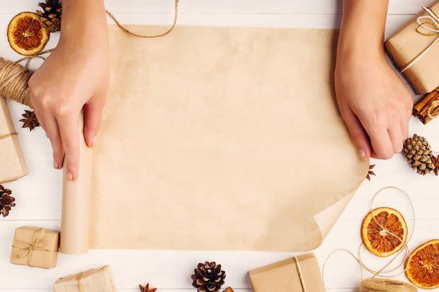 女性の手は、白いテーブルの上の乾燥オレンジ、シナモン、松ぼっくり、アニスの背景にクラフトペーパーロールを回しています。 、上面図、テキストのための場所。 Premium写真