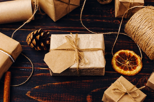 乾燥オレンジ、シナモン、松ぼっくり、木製のテーブルのアニスを背景にペーパークラフトのギフト Premium写真