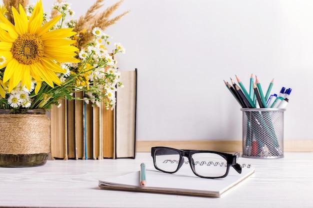 書籍、メガネ、マーカー、白い花瓶の花の花束 Premium写真