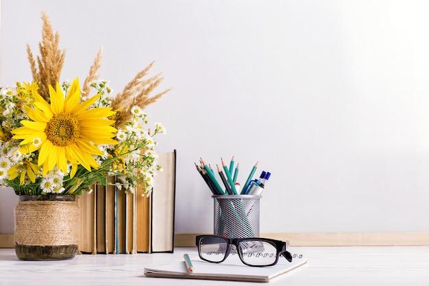 空のテーブルに木製チョークボードフレームと花瓶の花束 Premium写真