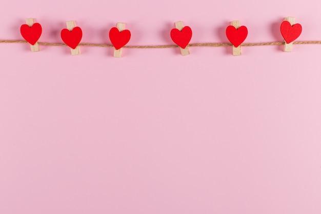 ピンクの背景のジュートロープに洗濯はさみで赤いハートが開催されます。コピースペース。 Premium写真