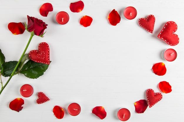 赤いバラ、花びら、キャンドル、白いテーブルの上の心。 Premium写真