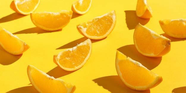黄色の背景、明るいパターンの壁紙にオレンジスライス。 Premium写真