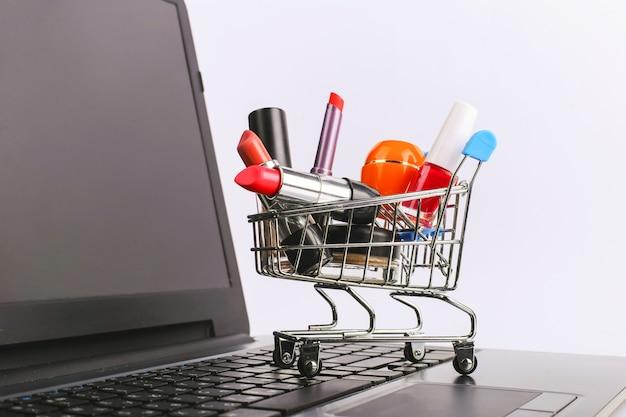 化粧品の買い物カゴはラップトップ上にあります。オンライン販売の概念 Premium写真