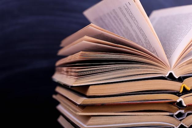 開いた本は机の上に積み重ねられ、黒板を背景にしています Premium写真