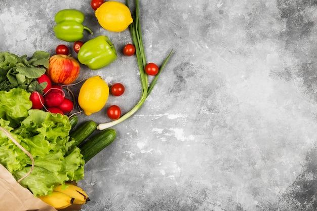 Различная здоровая еда в бумажной сумке на сером космосе. вид сверху, скопируйте пространство. пищевое пространство Premium Фотографии
