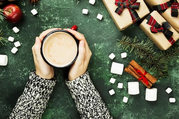 ホットチョコレートと緑の表面に休日のさまざまな属性を持つカップを保持している女性の手 Premium写真