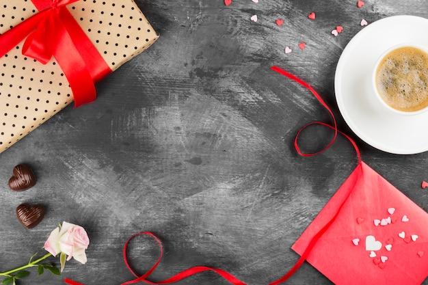 白いカップ、ピンクのバラ、赤いテープと暗い背景にチョコレートの贈り物にエスプレッソコーヒー。トップビュー、コピースペース。食品の背景。 Premium写真