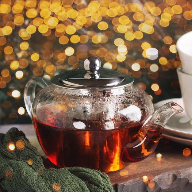 Горячий чай в стеклянном чайнике на зеленом фоне Premium Фотографии