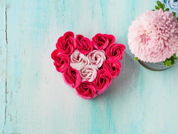 ハート型のパステルカラーのピンクの赤いバラ Premium写真