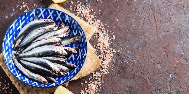 青魚。ピンクの塩の皿にアンチョビ Premium写真