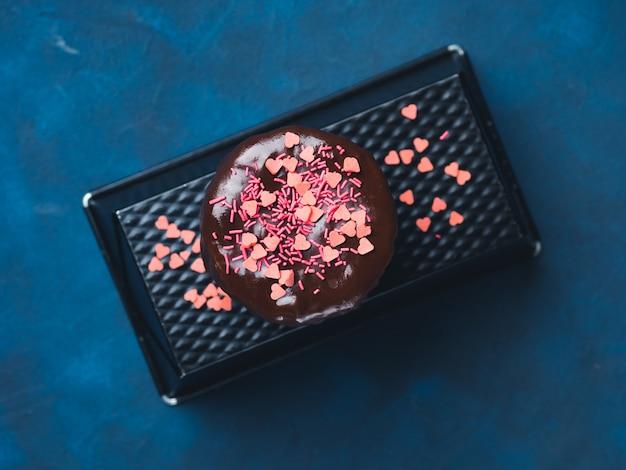 チョコレートグレーズ入りクリームチーズスポンジケーキとダークブルーにピンクのハートを振りかけます。誕生日パーティーバレンタイン母の日おやつ Premium写真