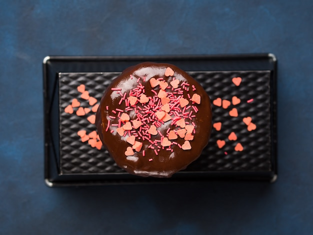 チョコレート艶出しとピンクのハートのクリームチーズスポンジケーキは、暗い青色の背景に振りかけます。 Premium写真