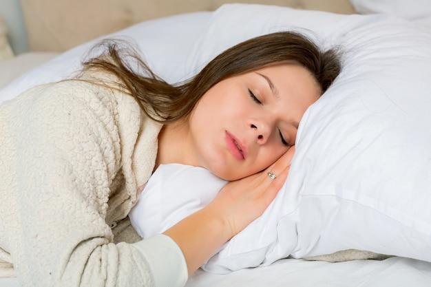 Портрет молодой женщины, спящей на кровати у себя дома Premium Фотографии
