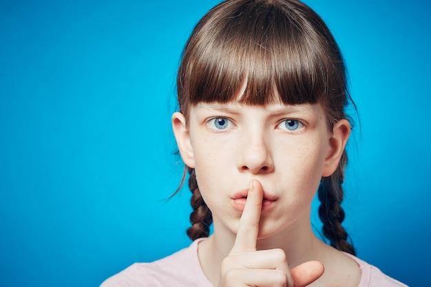 沈黙と静か。少女が視聴者を磨いています。唇に指。表情 Premium写真