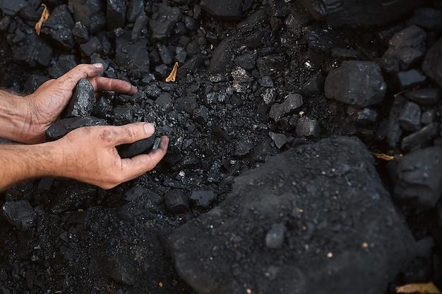 彼の家族に食糧を提供するために販売のための石炭の手を握って貧しい中年男 Premium写真