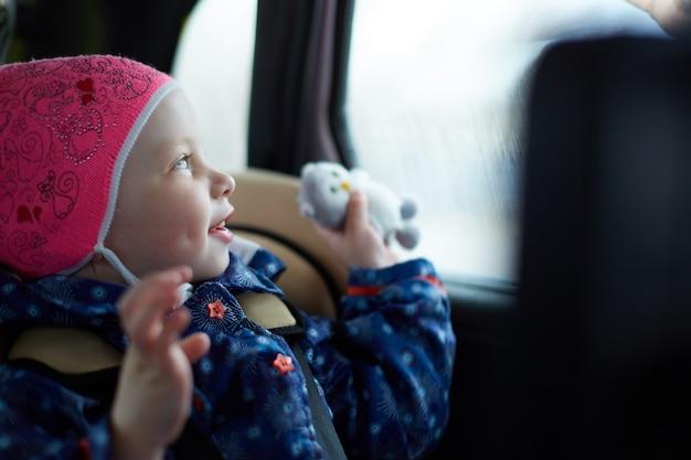 窓で車の後部座席のチャイルドシートに座っている青い目を持つ少女 Premium写真