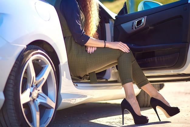 ビジネスの女性は高価な車に座っています。かかとの高い靴の足。 Premium写真
