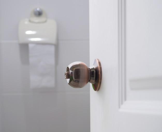 ドアの白いトイレの部屋を開けてください。 Premium写真