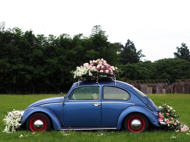 ビンテージ車は、芝生のフィールドに花で飾られました。 Premium写真