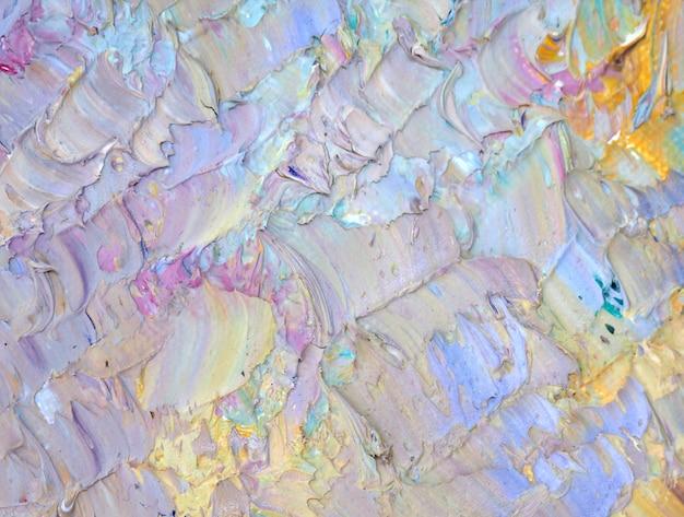 手は、テクスチャとカラフルな絵画の抽象的な背景を描きます。 Premium写真