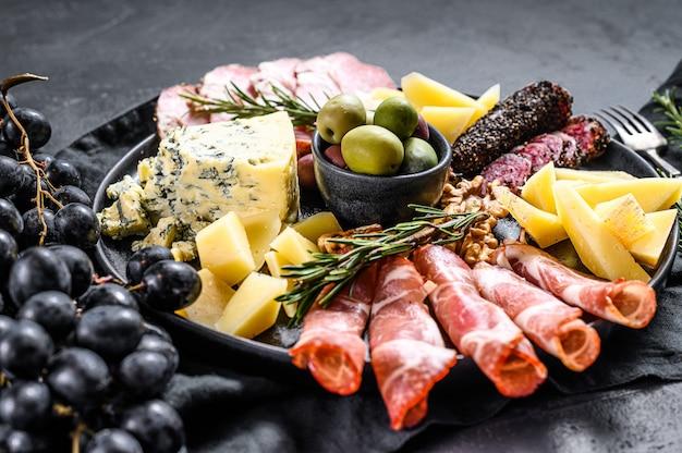 Типичный итальянский антипасто с ветчиной, ветчиной, сыром и оливками. черный фон. вид сверху Premium Фотографии