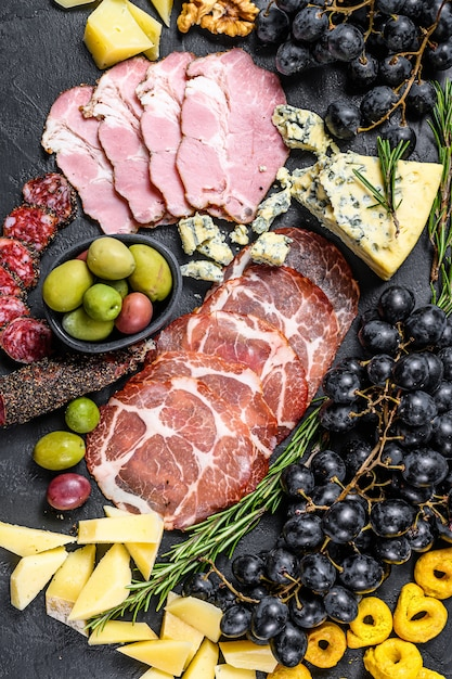 Антипасто с ветчиной, прошутто, салями, голубым сыром, моцареллой и оливками. черный фон. вид сверху Premium Фотографии