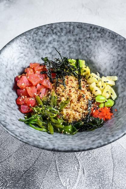 Тыкать миску с сырым тунцом и овощами. гавайское блюдо. концепция здорового питания. серый фон вид сверху Premium Фотографии