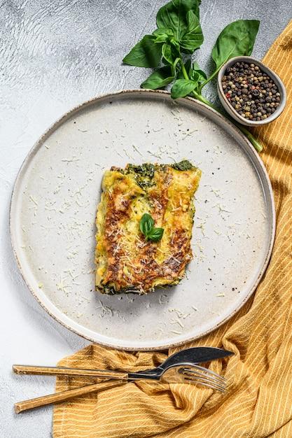 Запеченная фаршированная вегетарианская паста каннеллони с брокколи, шпинатом, базиликом и сыром. серый фон вид сверху. Premium Фотографии