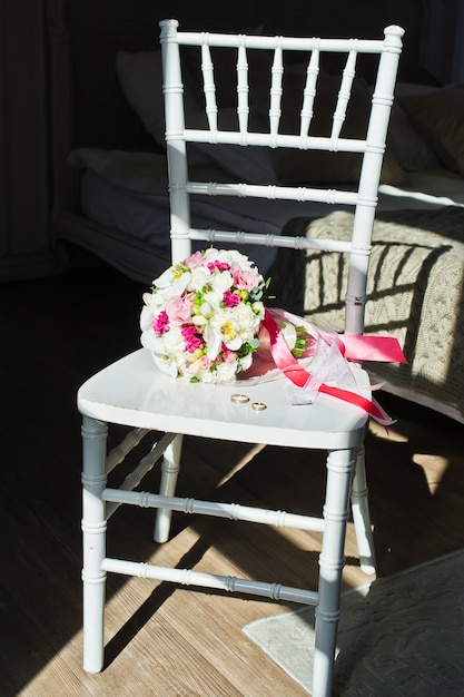 ブライダルブーケと椅子の上の金の結婚指輪。 Premium写真
