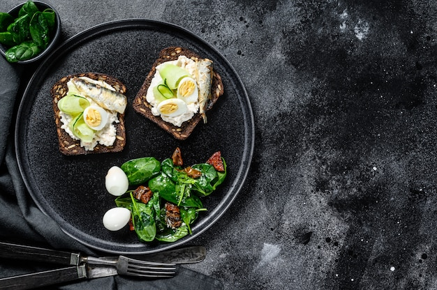 Бутерброды с сардинами, яйцом, огурцом и сливочным сыром, гарнир к салату со шпинатом и вялеными томатами. Premium Фотографии