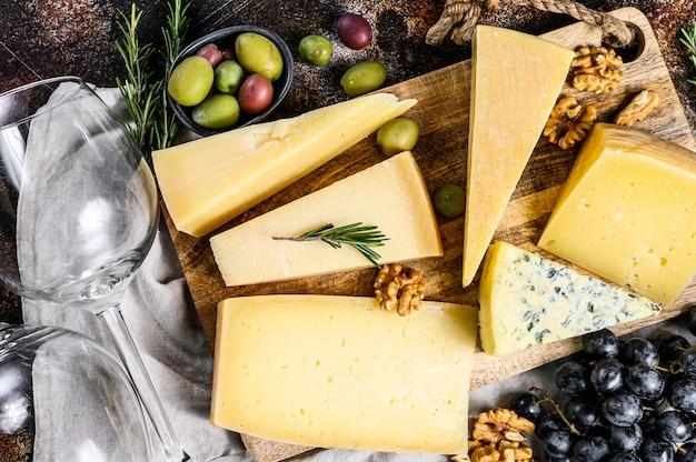Коллекция швейцарских, голландских, французских, итальянских сыров с орехами и виноградом. темная стена. вид сверху Premium Фотографии