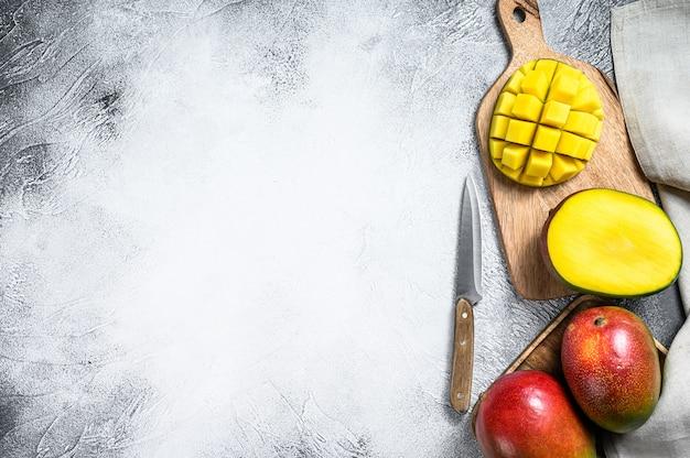 Спелые нарезанные фрукты манго на разделочную доску. вид сверху. копировать пространство Premium Фотографии