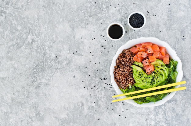 ポケ丼。材料:サーモン、アボカド、玄米、藻類。 Premium写真
