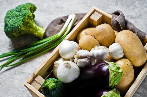 野菜用エコ包装、プラスチックフリー。野菜の箱:じゃがいも、玉ねぎ、ニンニク、ナス、ズッキーニ、ブロッコリー、ねぎ。ファーム。 Premium写真