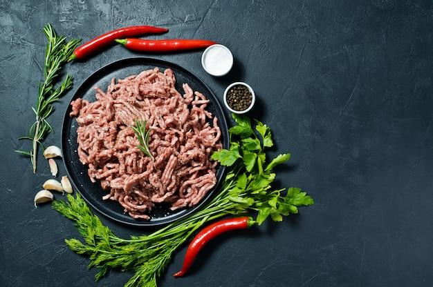 黒い皿に生のみじん切り。料理の材料、ローズマリー、唐辛子、ニンニク、塩、パセリ、ディル。 Premium写真